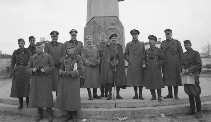 Finnish, German, Italian, French, American (Huthsteiner) and Japanese officers stand in front of Lenin's statue in Finnish-occupied Petrozavodsk 2 October 1942